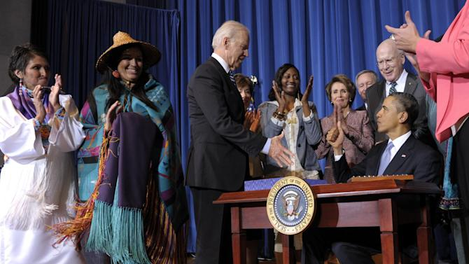 Vice President Joe Biden reaches to shake hands with President Barack Obama after the president signed the Violence Against Women Act,Thursday, March 7, 2013, at the Interior Department in Washington. From left are, Diane Millich, a member of the Southern Ute Indian Tribe in Colorado and domestic abuse survivor, Deborah Parker, Vice Chairwoman of the Tulalip Tribes of Washington State, Biden, Sen. Susan Collins, R-Maine, Tysheena Rhames, a trafficking survivor and advocate, House Minority Leader Nancy Pelosi of Calif., Sen. Mike Crapo, R-Idaho, and Sen. Patrick Leahy, D-Vt.,  (AP Photo/Susan Walsh)
