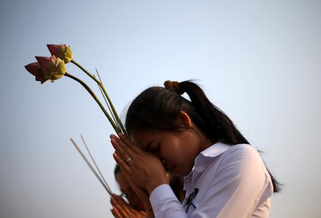 Two girls offer prayers to Cambodia's former King Norodom Sihanouk in Phnom Penh, Monday, Feb. 4, 2013. Sihanouk's body had been lying in state at the Royal Palace after being flown from Beijing where