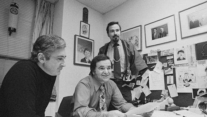 """FILE - In this 1972 file photo, """"Mad"""" magazine Editor Al Feldstein, center, sits with Art Director John Putnam, left, and a freelancer named Jack, at the magazine's New York headquarters. Feldstein, whose 28 years at the helm of Mad transformed the satirical magazine into a pop culture institution, died Tuesday, April 29, 2014. He was 88. (AP Photo/Jerry Mosey, File)"""