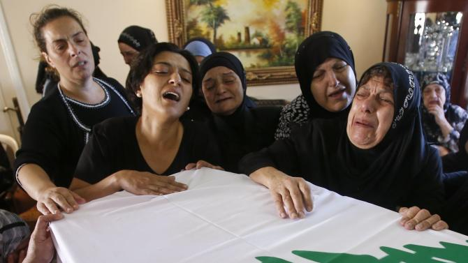 The mother of a Lebanese soldier killed by a roadside bomb mourns with relatives at his coffin during his funeral in Sidon
