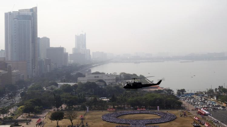 A helicopter hovers over a female symbol formed by people, as part of celebrations for International Women's Day in Manila