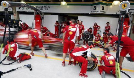 Ferrari Formula One mechanics practise a pit stop with the car of driver Fernando Alonso of Spain at Interlagos race track in Sao Paulo