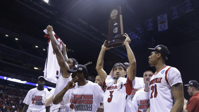 Louisville guard Peyton Siva (3) holds up the regional trophy as Louisville players celebrate their 85-63 win over Duke in  the Midwest Regional final in the NCAA college basketball tournament, Sunday, March 31, 2013, in Indianapolis. (AP Photo/Michael Conroy)