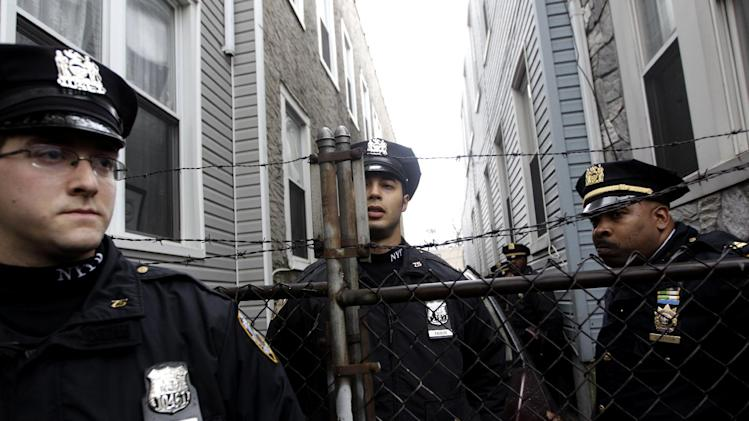 Police officers stand guard during a tour of foreclosed homes by Occupy Wall Street activist in the East New York neighborhood of the Brooklyn borough of New York, Tuesday, Dec. 6, 2011. Finding it increasingly difficult to camp in public spaces, Occupy protesters across the country are reclaiming foreclosed homes and boarded-up properties, signaling a tactical shift for the movement against wealth inequality. Groups in more than 25 cities held protests Tuesday on behalf of homeowners facing evictions.(AP Photo/Mary Altaffer)