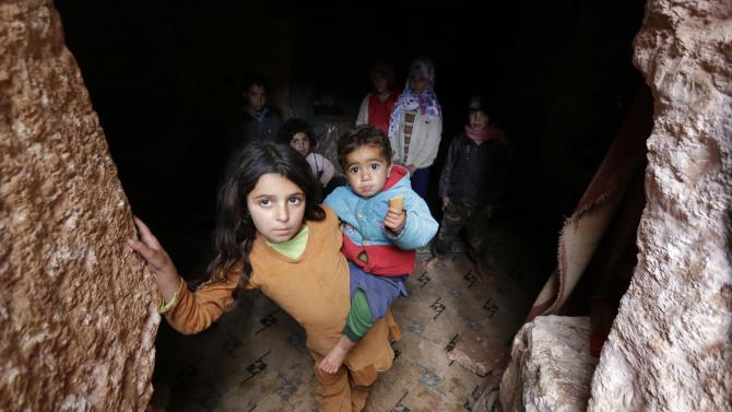 Mariam carries her brother as she stands with other children at an underground ancient cemetery in Jabal al-Zawiya in the southern countryside of Idlib