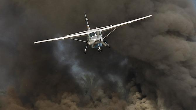 An airplane carrying aid for flood victims lands at Kalay airport as smoke raises from a fire near a petrol station in Kalay township at Sagaing division