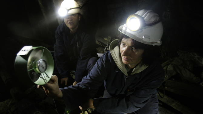 Woemn coal miners Sakiba Colic, left, and Semsa Hadzo, right, Bosnian coal technologists, are checking air flow and temperature at 450 meters underground in the shaft of the coal mine in Breza, 20 kms north of Sarajevo, Bosnia, on Wednesday, Jan. 16, 2013.  The mine in Breza is the only one in Bosnia where a group of women work deep underground in the coal mines alongside their male colleagues, a legacy of communism, but they're set to retire in three years, marking the end of an era for this community where almost everybody is connected to the coal mine. The shafts and elevators echo with laughter and tales of their grandchildren as women miners work alongside their male counterparts.(AP Photo/Amel Emric)