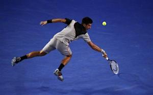 Novak Djokovic of Serbia hits a return to Stanislas Wawrinka of Switzerland during their men's singles quarter-final tennis match at the Australian Open 2014 tennis tournament in Melbourne