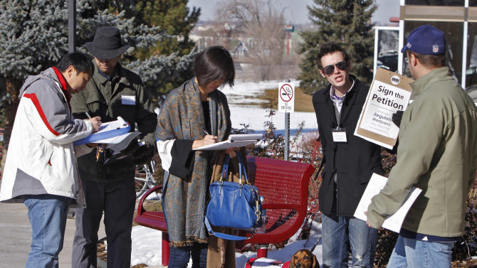 FILE - In this Dec. 8, 2011, file photo taken at the Department of Motor Vehicle office in Littleton, Colo., volunteers Emmett Reistroffer, second from left, and Justin Dreyer, second from right, collect signatures on a petition to legalize marijuana in Colorado. Voters in Colorado won't just decide whether to go red or blue this fall but also green _ as in weed or grass. Marijuana and a question about whether to legalize it are on Colorado ballots in November 2012. President Barack Obama and Republican challenger Mitt Romney have identical stances on pot legalization _ they oppose it. (AP Photo/Ed Andrieski, File)