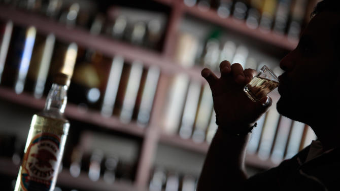 """In this April 11, 2013 photo, a man drinks cachaca, Brazil's national spirit, at the """"Adega da Cachaca"""" cellar in Brasilia, Brazil. With Brazil's cool factor rising as the country gears up for next year's soccer World Cup and the 2016 Olympics, producers of the national spirit cachaca hope the hype will push up sales as well. (AP Photo/Eraldo Peres)"""