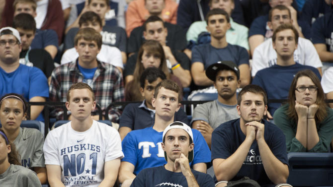 Students listen as Connecticut men's basketball coach Jim Calhoun announces his retirement in Storrs, Conn., Thursday, Sept. 13, 2012. The 70-year-old Hall of Famer ran the men's program for 26 years and won three national titles. Assistant coach Kevin Ollie, who played for Calhoun, will be the Huskies' new coach. (AP Photo/Jessica Hill)