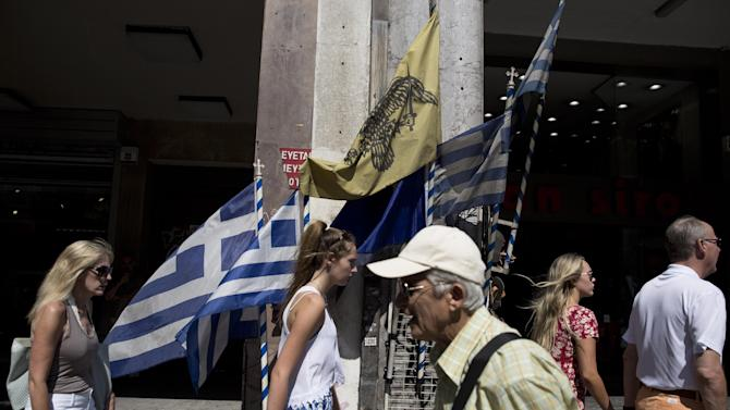 "Tourists and a lottery ticket vendor walk past various flags in Athens, on Friday, July 3, 2015. The brief but intense campaign in Greece's critical bailout referendum ends Friday, with simultaneous rallies in Athens for ""Yes"" and ""No"" supporters in what an opinion poll shows will be a very close race. (AP Photo/Petros Giannakouris)"