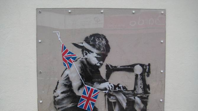 "This is an undated image of an art work from  British artist Banksy made available by Haringey Council Wednesday Feb. 20, 2013. The stencil by the famed, secretive graffiti artist of a young boy sewing Union Jack bunting on an antique sewing machine appeared on the side of a north London bargain store last May. Soon the gritty Turnpike Lane area was drawing art lovers keen to see Banksy's typically cheeky take on the Diamond Jubilee celebrations of Queen Elizabeth II's 60 years on the British throne. Last week it vanished, leaving nothing but a rectangle of exposed brick — only to reappear on the website of a Miami auction house. Listed as ""Slave Labor (Bunting Boy),"" it is due to be sold Saturday with an estimated price of between $500,000 and $700,000. (AP Photo/Haringey Council)  NO ARCHIVE"