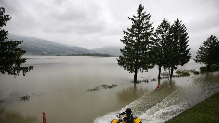A quad biker drives on a flooded street along lake Lauerzersee, in Lauerz, Switzerland, Sunday, June 2, 2013. Heavy rainfalls cause flooding along rivers and lakes in Germany, Austria, Switzerland and the Czech Republic. (AP Photo/Keystone, Alexandra Wey)