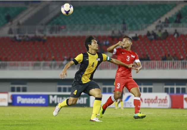 Mohamad Sahil Suhaimi of Singapore and Mohamad Fadhli Mohd Shas of Malaysia fight for ball during soccer men's bronze medal match at 27th SEA Games in Naypyitaw