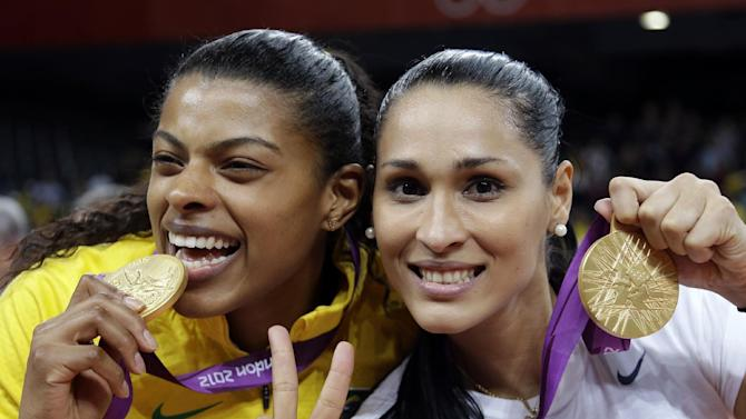 FILE - In this Aug. 11, 2012 file photo, Brazil's Fernanda Rodrigues, left, and Jaqueline Carvalho, pose with their gold medals for women's volleyball at the 2012 Summer Olympics, in London. Brazil may be on track for a record performance at the home Olympics in 2016. The Brazilian Olympic Committee is aiming for a record number of medals after the country significantly increased investments to train its athletes ahead of the games. The goal is to nearly double the 17 medals earned at the 2012 London Games and put Brazil in the top 10 in the overall number of medals, which officials say would be an outstanding feat for the hosts of the first Olympics in South America. (AP Photo/Chris O'Meara, File)