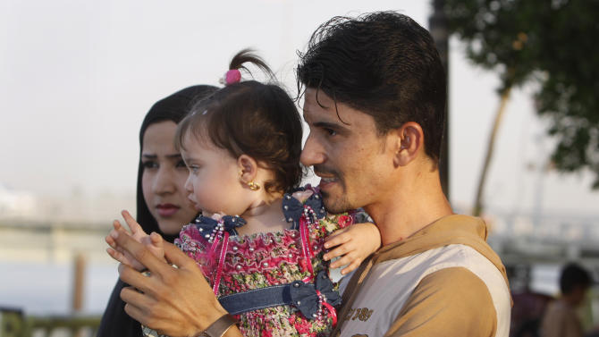 """In this Sept. 9, 2012 photo, Akram Hashim, 25, holds his daughter as he and his wife picnic at the riverbank in Basra, Iraq, 340 miles (550 kilometers) southeast of Baghdad. """"A stable government job to help my family is what is needed,"""" said Hashim, a Shiite who lives with his wife and daughter in his parents' home with six other relatives. """"It is very hard to get a good job."""" (AP Photo/Nabil al-Jurani)"""