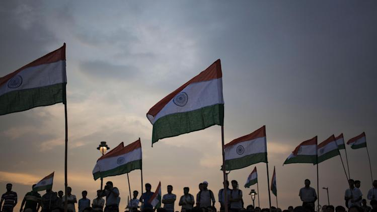 Indians hold their national flags and watch a musical tribute to war heroes on the 15th anniversary of India's victory in the Kargil War, in New Delhi, India, Saturday, July 26, 2014. The 1999 conflict with Pakistan raged for three months across the disputed Kashmir region and nearly brought the nuclear neighbors to a war. (AP Photo/Tsering Topgyal)