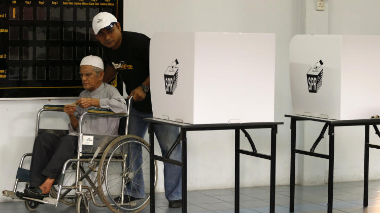 An elderly man on wheelchair is helped to cast his ballot during for the general elections, Sunday, May 5, 2013. Malaysians have begun voting in emotionally charged national elections that could see the long-ruling coalition ousted after nearly 56 years in power. (AP Photo/Vincent Thian)