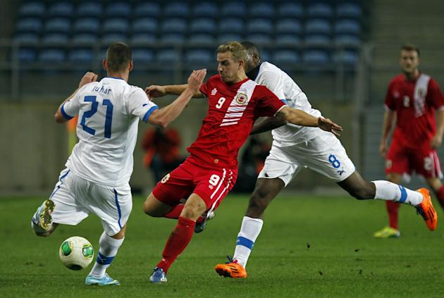 Gibraltar's Adam Priestley, centre, vies for the ball with Slovakia's Martin Juhar, left, and Karim Guede during a friendly soccer match between Gibraltar and Slovakia at the Algarve stadium in Faro,