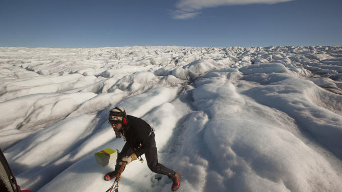 In this July 19, 2011 photo, attached by rope to a waiting helicopter, researcher Carl Gladish walks back after deploying a GPS seismometer, or GeoPebble, to track glacial movement on Jakobshavn Glacier, near Ilulissat, Greenland. Chief researcher David Holland, hopes to eventually deploy scores of the devices to measure ice loss in Greenland. (AP Photo/Brennan Linsley)
