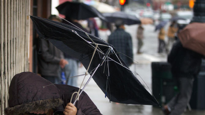 A commuter faces a gust of wind in the Chinatown district of Los Angeles on Friday, April 13, 2012. A powerful spring storm that zapped an airliner with lighting in San Francisco moved across California on Friday, threatening the state with thundershowers, fierce winds and blinding snow flurries in the mountains. (AP Photo/Damian Dovarganes)