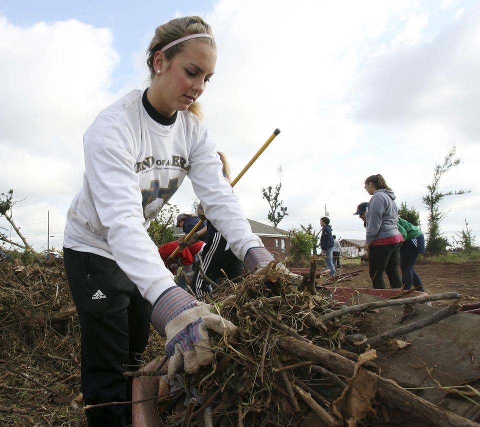 In this photo taken Oct. 19, 2011, Notre Dame pole vaulter Chrissy Finkle loads a wheelbarrow with debris in Tuscaloosa, Ala. Twenty-four student athletes from Notre Dame were in Tuscaloosa volunteering time during their fall break to help clean up tornado damaged areas. (AP Photo/The Tuscaloosa News, Robert Sutton)