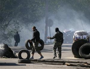 Pro-Russian men stand guard at a checkpoint which was left by Ukrainian security force officers near Slaviansk