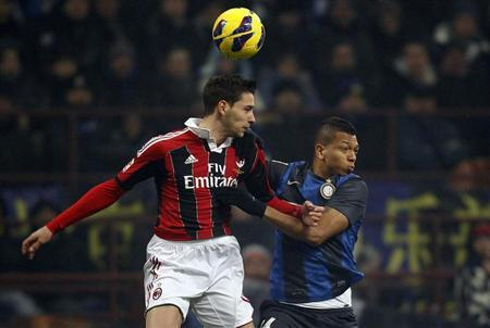 AC Milan's De Sciglio jumps for the ball with Inter Milan's Guarin during their Italian Serie A soccer match in Milan