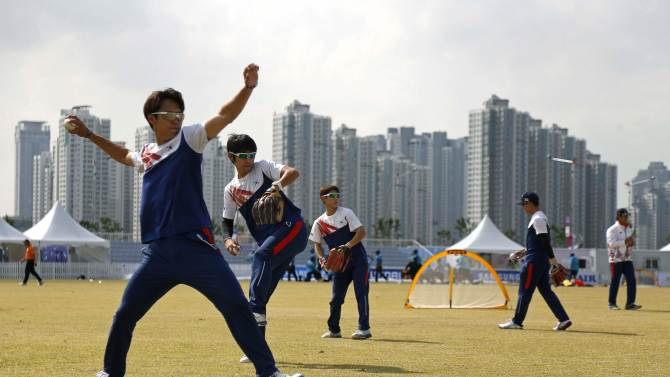 South Korea's cricket team warm up, using baseballs and baseball gloves, before their men's Twenty20 quarter final cricket match against Sri Lanka at the 17th Asian Games in Incheon