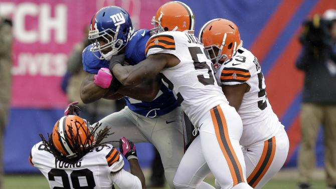 New York Giants running back Ahmad Bradshaw (44) is tackled by Cleveland Browns middle linebacker D'Qwell Jackson (52),  Craig Robertson (53) and  Usama Young (28) during the first half of an NFL football game Sunday, Oct. 7, 2012, in East Rutherford, N.J. (AP Photo/Kathy Willens)
