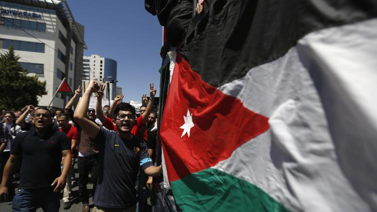 Jordanian protesters shout slogans as they walk past a Jordanian flag, during a demonstration to calling for an end to the Israeli offensive in the Gaza Strip, in Amman