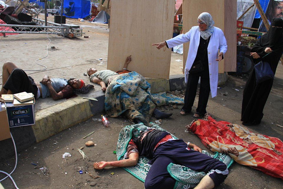 Injured supporters of ousted Islamist President Mohammed Morsi lie on the ground after Egyptian security forces clear a sit-in camp set up by supporters of Morsi in Nasr City district, Cairo, Egypt, Wednesday, Aug. 14, 2013. Egyptian security forces, backed by armored cars and bulldozers, moved on Wednesday to clear two sit-in camps by supporters of the country's ousted President Mohammed Morsi, showering protesters with tear gas as the sound of gunfire rang out at both sites. (AP Photo/Ahmed Gomaa)