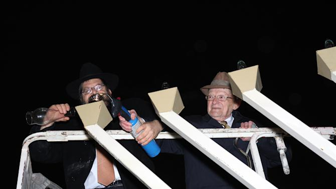 """Rabbi Areyah Kaltmann of the Lori Schottenstein Chabad Center in New Albany, prepares to light the menorah with the help Holocaust survivor, Abe Weinrib, Saturday, Dec. 8, 2012 in Columbus, Ohio. The start of Hanukkah on Saturday night had special meaning for Weinrib, a Holocaust survivor in Ohio who turns 100 next week. As a victim of the Holocaust, """"it's a miracle I survived,"""" Weinrib, who will turn 100 on Tuesday. (AP Photo/Lori Schottenstein Chabad Center, Laurence Gilbert)"""