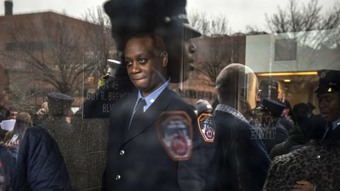 A firefighter is photographed through glass after a graduation ceremony for nearly 200 Fire Department paramedics and emergency medical technicians at York College in the Queens borough of New York