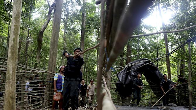 Security forces and rescue workers inspect an abandoned camp in a jungle in Thailand's southern Songkhla province