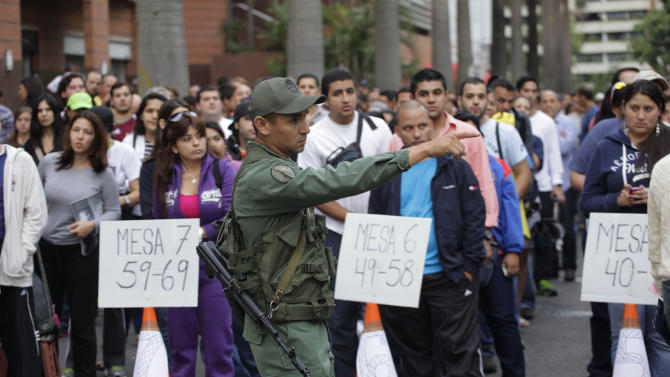 A soldier points as people wait in line to vote in the presidential election outside a polling station in Caracas, Venezuela, Sunday, Oct. 7, 2012. President Hugo Chavez is running for re-election against opposition candidate Henrique Capriles. (AP Photo/Ramon Espinosa)