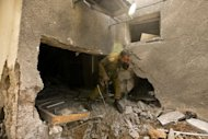 An Israeli soldier inspects the damage to a house following a rocket attack on the Israeli Kibbutz Beeri from the Gaza Strip on October 24. The latest escalation began on Tuesday evening, shortly after the end of a high-profile visit to Gaza by the emir of Qatar, when militants fired six rockets at southern Israel