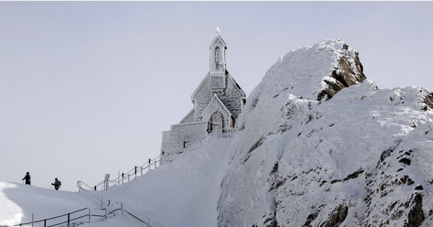 Hikers make their way near the frost covered Wendelstein church, Germany's highest church, at 1838 meters (6030 feet) on the Wendelstein mountain near Bayrischzell, southern Germany, on Thursday, Feb.
