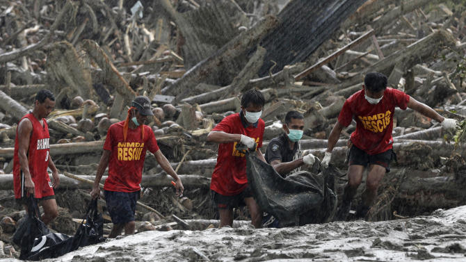 FILE - In this Dec. 7, 2012 file photo, rescuers retrieve flash flood victims from the debris of Typhoon Bopha, three days after the powerful storm swept through New Bataan township in the Compostela Valley in southern Philippines. In 2012 many of the warnings scientists have made about global warming went from dry studies in scientific journals to real-life experience. (AP Photo/Bullit Marquez, File)