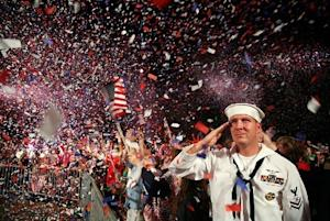 Communication Specialist 2nd Class Scott Webb salutes as the American flag is presented on stage during the Boston Pops Fireworks Spectacular at the Charles River Esplanade