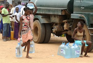People carry water at a distribution point on September …