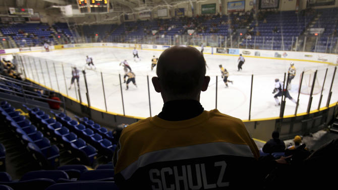 "FILE - In this March 3, 2010, file photo, Johnstown Chiefs fan Robert Schulz watches a minor-league hockey game against the Kalamazoo Wings at the Cambria County War Memorial Arena in Johnstown, Pa. The Chiefs moved to Greenville, S.C., from Johnstown two years ago. A new group of investors are trying once again to support a hockey team to play in this same arena in the gritty western Pennsylvania city whose rich minor-league hockey history produced the cult movie hit ""Slap Shot,"" this time by relocating a junior league franchise from Alaska. (AP Photo/Carolyn Kaster, File)"