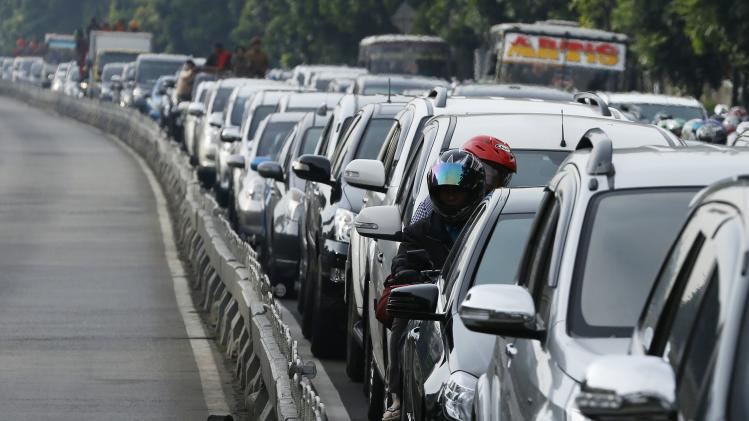 People on a motorcycle look on while in between other vehicles in a gridlocked street in Jakarta