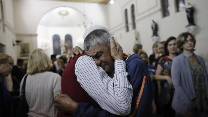 Homeless man is embraced by a man during a mass at Sao Miguel Arcanjo church before a free Christmas dinner in Sao Paulo