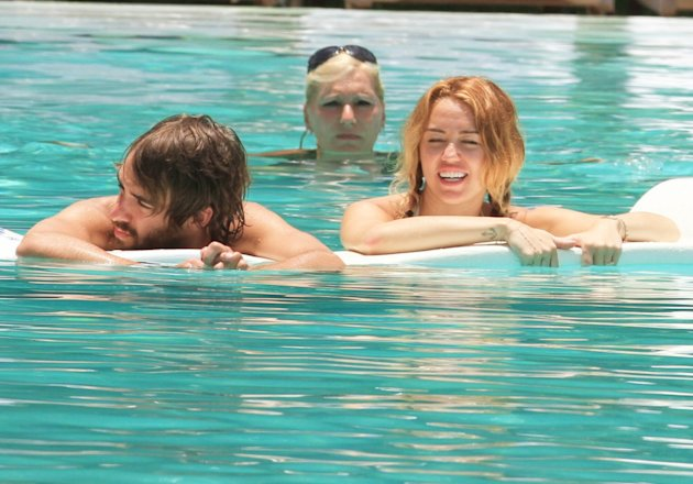 USA ONLY Miley Cyrus gets VERY close to a male companion in a Miami pool