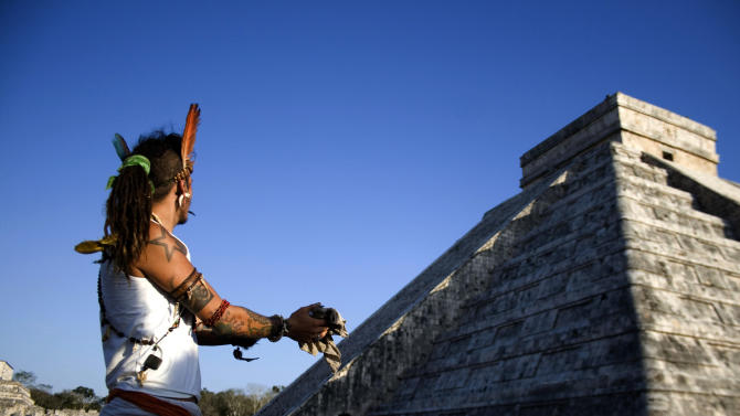 FILE - In this March 20, 2010 file photo, a man performs a ritual as he looks toward the descent of the Kukulkcan serpent, whose image is seen illuminated along the edge of the stairs of the Mayan Chichen Itza pyramid, during the Spring equinox in Chichen Itza, Mexico. A chorus of books and movies tried to link the Mayan calendar to rumors of impending disasters ranging from rogue black holes and sun-storms to the idea that the Earth's magnetic field  could 'flip' on that date. Archaeologists says there is no evidence the Maya ever made any such prophesy. (AP Photo/Israel Leal, File)