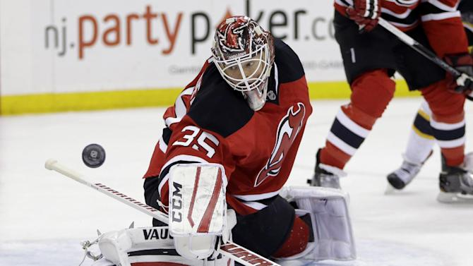 New Jersey Devils goalie Cory Schneider deflects a shot by the Boston Bruins during the first period of an NHL hockey game, Friday, Feb. 27, 2015, in Newark, N.J. (AP Photo/Julio Cortez)