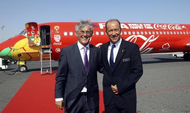 Soccer coach Bora Milutinovic and FIFA representative Gabriel Calderon pose in front of the FIFA World Cup trophy plane following its arrival in Doha
