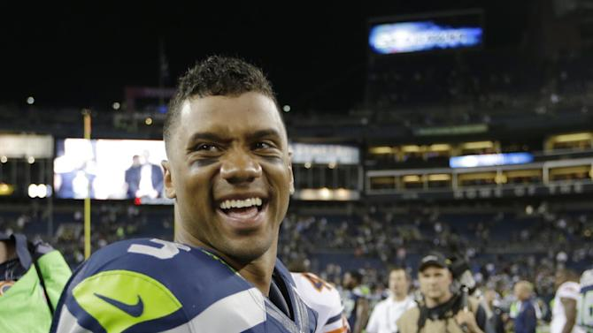 Seattle Seahawks quarterback Russell Wilson smiles after the Seahawks' 34-6 win over the Chicago Bears in a preseason NFL football game, Friday, Aug. 22, 2014, in Seattle